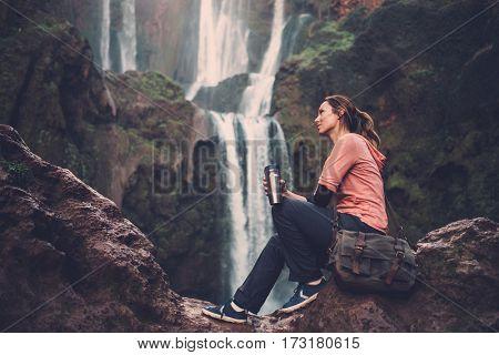 Pensive woman with coffee mug near Ouzoud waterfall in Morocco.
