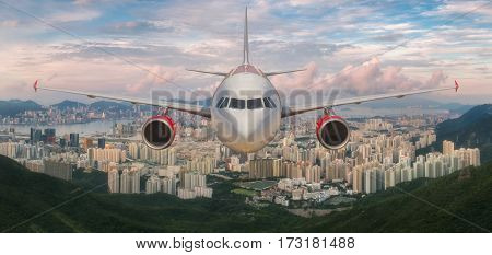 Airplane over Hongkong island with city scape in day time below