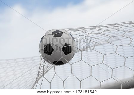 soccer ball in goal with blue sky backgroung