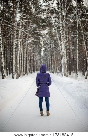 Woman In Warm Clothes On A Blurred Winter Background