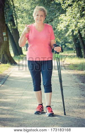 Vintage Photo, Elderly Senior Woman Practicing Nordic Walking And Showing Thumbs Up, Sporty Lifestyl