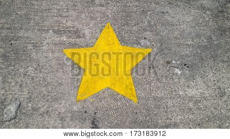 Yellow painting star on concrete texture background