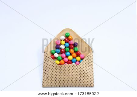 Colorful gumballs spill out of envelope onto white background open for copy.