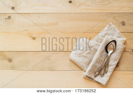 top view of three vintage spoons on a linen fabric on wooden boards background with copy negative space