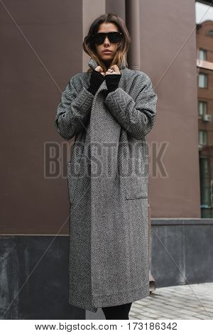 Young fashionable female wearing gray coat looking at camera through the sunglasses. Vertical outdoors shot.