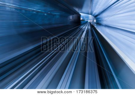 Blurred motion subway moving into tunnel abstract background