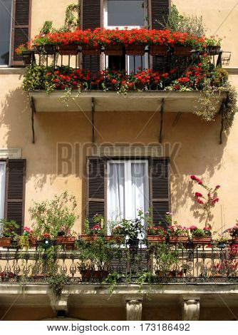 Building in Italy with two balconies and lots of flowers