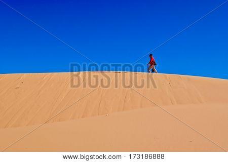 Man waking on sand dunes. Coral Pink Sand Dunes Park. Cedar City. Kanab. Utah. United States.