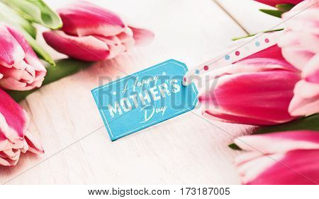 Spring composition with tulips and greeting label on white wooden background