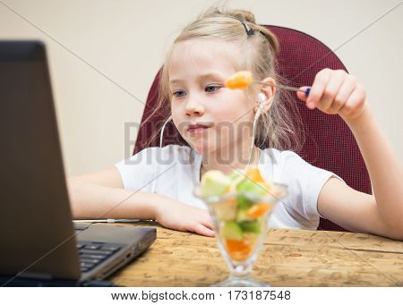 Girl eating fruit salad at the laptop. Healthy Eating child at the computer.