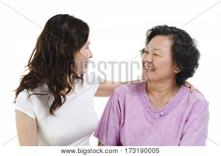 Portrait of Asian senior mother and adult daughter talking and looking at each other, isolated on white background.