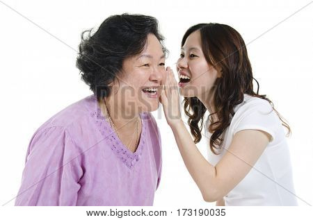 Portrait of Asian adult daughter sharing secrets to her senior mother, isolated on white background.