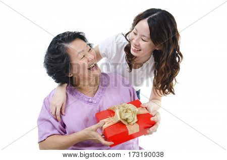 Celebrating mothers day or birthday. Portrait of Asian senior parent getting a present box from adult daughter, isolated on white background.