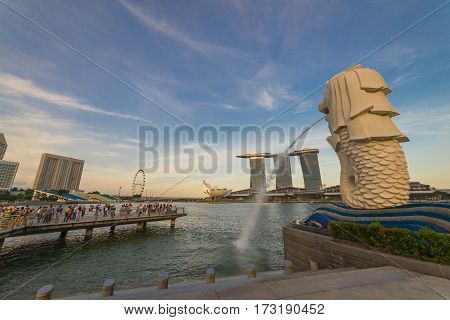 AUGUST 17 2016 SINGAPORE : The Merlion is a traditional creature with a lion head and a body of a fish seen as a symbol of Singapore.Landscape of the Singapore landmark financial district at twilight sunset scene with blue sky and clouds. Singapore downto