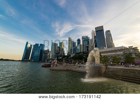 AUGUST 17 2016 SINGAPORE : The Merlion is a traditional creature with a lion head and a body of a fish seen as a symbol of Singapore.Landscape of the Singapore landmark financial district at sunset