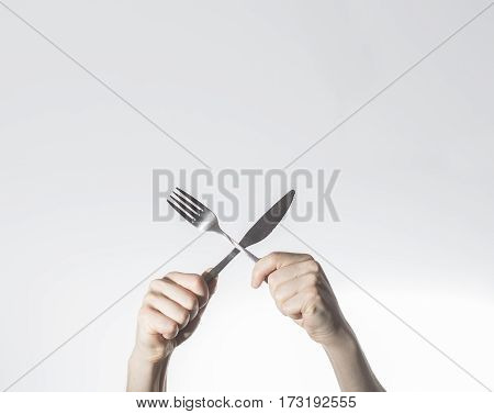 breakfast concept hands hold knife and fork crosed Space for text free space