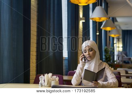 Islamic beautiful girl talking on the phone in restaurant Russia