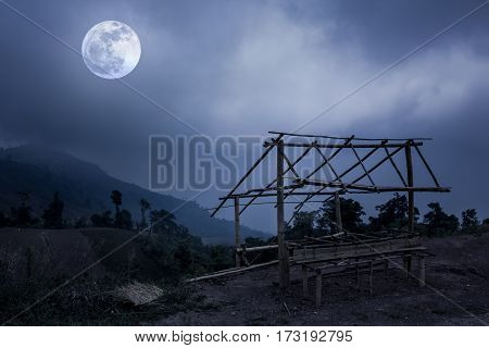 Little Bamboo Hut And Mountain Peaks. Silhouettes Of Trees With Sky And Full Moon.