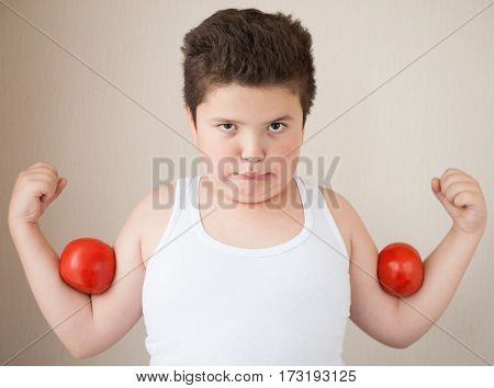 thick boy in t-shirt shows muscles with red tomatoes on his biceps poster