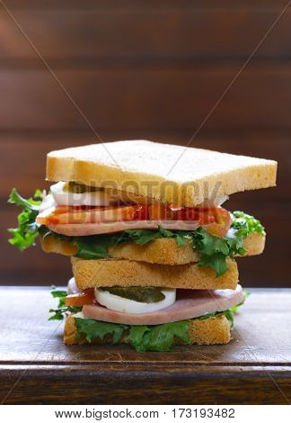 sandwich with ham, tomato, egg and pickles