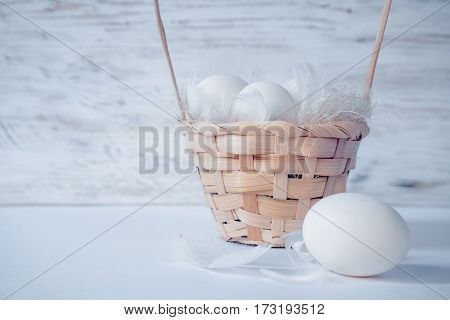 easter eggs in basket on white wooden background