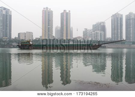 Long cargo ship in the water on the background of buildings.