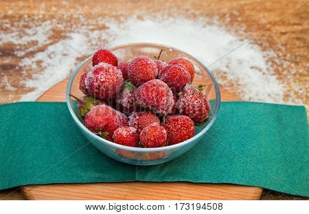 frozen strawberries are medium in size in a glass container on a wooden stand