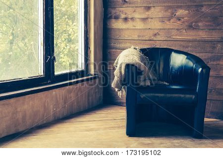 Comfortable black leather armchair with warm cozy knitted plaid near the window in country house with wooden walls. Winter rest corner concept. Copy space.