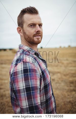 Portrait of farmer standing in the field on a sunny day