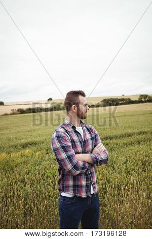 Thoughtful farmer standing with arms crossed in the field on a sunny day