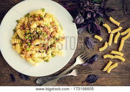 Fusilli with prosciutto and green pease on old wooden background. Traditional Italian pasta with fresh basil. Top view.