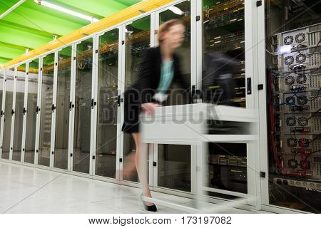 Technician pushing cart on hallway in server room