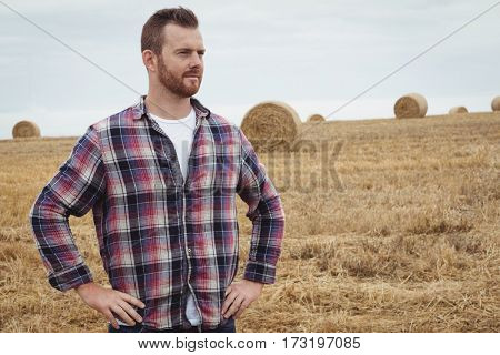 Farmer standing with hands on hips in the field on a sunny day