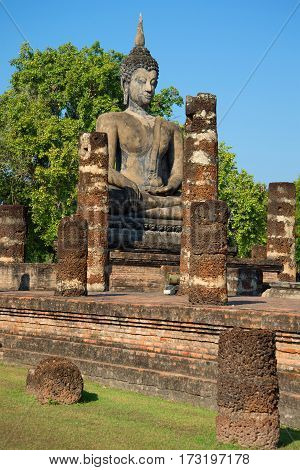Ancient sculpture of a seated Buddha on the ruins of the temple of Wat Chana Songkram. Sukhothai, Thailand