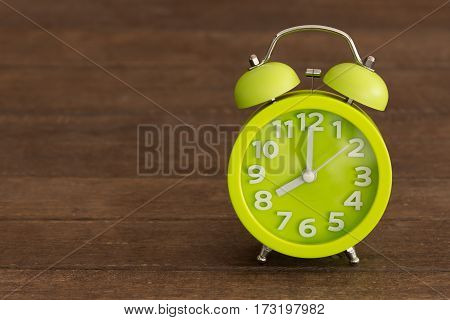alarm clock on wooden table in a dark background.