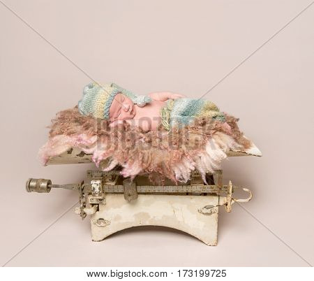 Lovely baby sleeping on old rusty scales, wearing multicolored pants, on soft pillow