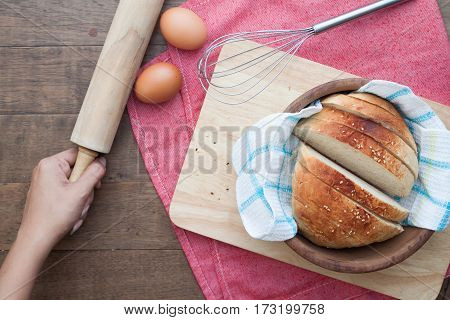Homemaker holding rolling pin with sliced homemade bread on wood background