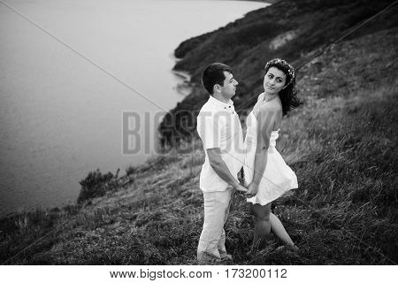 Loved Couple In Love At Amazing Landscape Against Cliff Rocks. Black And White Photo.
