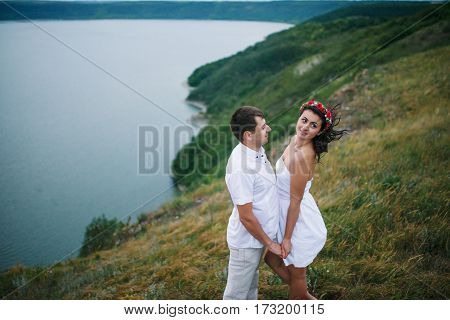 Loved Couple In Love At Amazing Landscape Against Cliff Rocks.