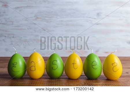 candles eggs with green grass preparing for easter on wooden background