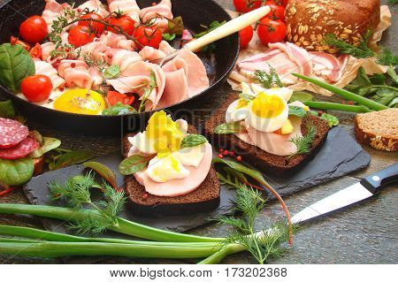 Assortment of delicatessen smoked meat bacon eggs vegetables tomatoes herbs in rustic style
