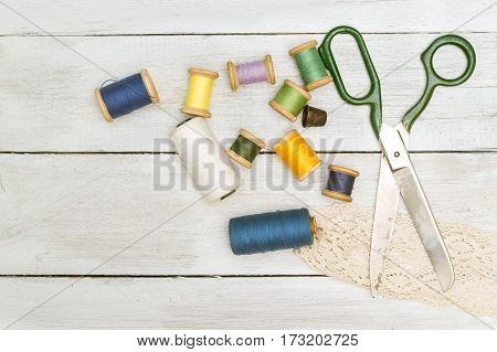 the old scissors spools of thread thimble on a wooden background. flat lay