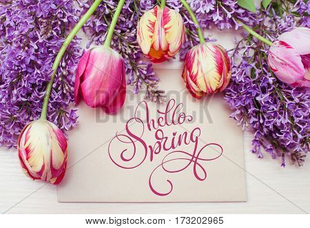frame from tulips and lilac and place for text greeting card and text Hello Spring. Calligraphy lettering.