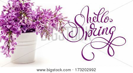 white bucket and lilac on a white background and text Hello Spring. Calligraphy lettering.