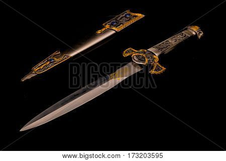 A ceremonial dagger alongside a jeweled sheath against a reflective black background