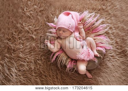 tender sleeping newborn baby in pink cap on a gentle pink background beige fur and wool