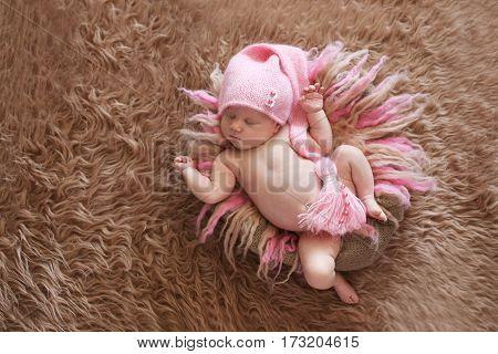 tender sleeping newborn baby in pink cap on a gentle pink background beige fur and wool