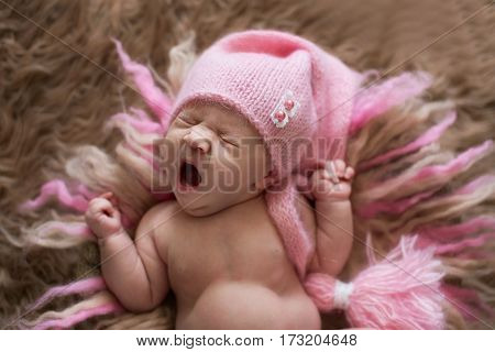 sweet newborn baby in pink cap yawns and stretches wakes on beige and pink wool
