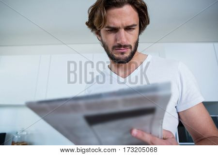 Man reading newspaper in kitchen at home