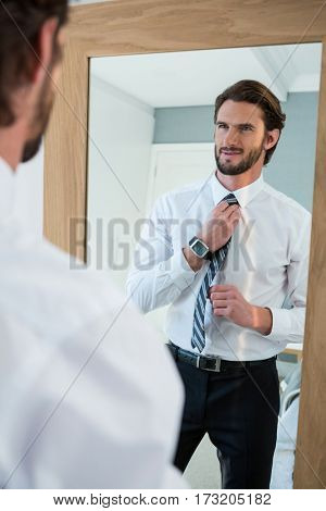 Man getting dressed in bedroom while looking at mirror at home
